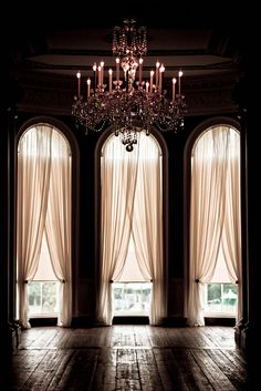 arched high windows, dramatic curtains + antique chandelier.