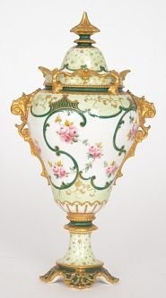 A Royal Crown Derby twin handled vase and spire cover decorated with pink floral sprigs against a tonal green ground with gilt foliate scrolls, the handles and collar neck with applied moulded gilt mounts, printed mark to base,