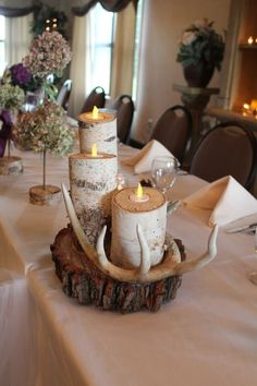 Table top Rustic wedding table decorations: birch tree candles and antlers with tall floral centerpieces. These would be perfect for a mountain themed wedding reception. Birch Centerpieces, Rustic Wedding Centerpieces, Wedding Table Decorations, Centerpiece Decorations, Wedding Rustic, Antler Wedding Decor, Table Wedding, Masculine Centerpieces, Antler Decorations