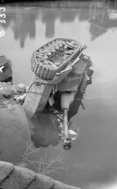 A StuG III Ausf. G (late) sits turned onto its side in a river near Putanges, France, 20 August 1944.