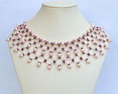 Este collar de collar es tejido de grano de perlas de agua dulce color rosa pálidas y muchos colores de Rocallas de cristal. El collar es más ancho en la frente y es más estrecho en los hombros y la espalda. La longitud de este collar es de 39cm (15 3/8) y no puede ser extendido. El cierre es tipo caja de filigrana metal plata