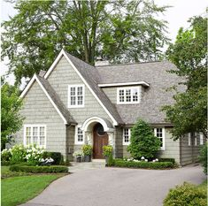 """Love how they have matched an """"eyebrow"""" overhang to the arch in the front door.  Very inviting profile on this home."""