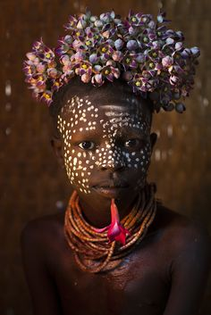 "Africa | ""Child from the Omo Valley with flowers"".  Korcho, Omo, Ethiopia 