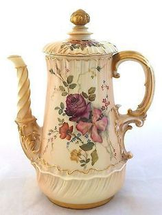 Item Description A rare antique china coffee pot by Royal Worcester, hand painted with various flowers and foliage on a blush ivory ground (pattern number 1613) and dating to 1893. The spout has a sp