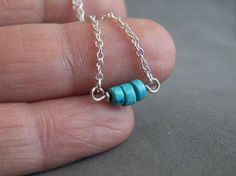 These three small turquoise rondelles are mounted on a sterling silver setting hanging on a sterling silver chain.  The necklace is fastened by a lobster clasp.  Minimalist necklace, perfect for every day and as a gift.  For centuries Turquoise has been recognized as possessing the power to protect riders from injury due to falls. It is believed that turquoise is a purification stone. It dispels negative energy and can be worn to protect against outside influences or pollutants in the…