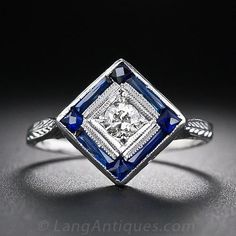 There's a lot going on in this strikingly dramatic Art Deco diamond ring from the 1930s. The ring features a diamond within a diamond (shaped top, that is) that radiates from within a triple milgrained setting, which, in turn, is framed by eight deep royal blue, precision-cut synthetic calibre sapphires (which are original to both the ring and the period). The decoratively pierced and engraved gallery smoothly blends into the ring shank, making for a stunning and sophisticated vintage jewel.