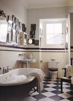 modern meets vintage bathroom // black and white checker floor // free standing claw foot tub // modern stripe on wall