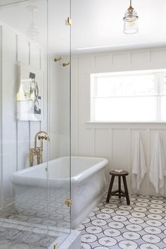 White millwork, brass fixtures and modern freestanding bathtub, open walk in shower, and glass pendant lamp. Chic, minimal, modern beach house vibes.