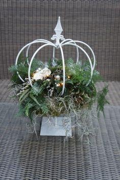 metalen frame - kroon op voet met bloemstuk. Je kan ook metalen kroontje van de action op een taartplateau zetten (betonnen kaarsenstandaard (kluis))
