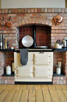 Love the Aga stove, brick, wood and copper pot accents.
