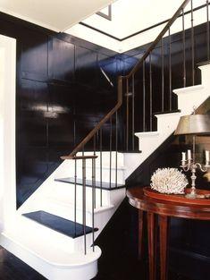 shiny black + white stairs + brass rail