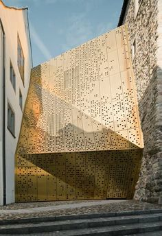 Hundreds of circular holes puncture a faceted bronze extension to a fortified museum in Rapperswil-Jona, Switzerland