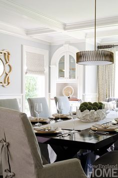 Neutral colors and simple window treatments let the dining room's classic…