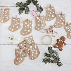 Calendrier de l'avent DIY composé de 24 jolies chaussettes numérotées en toile de jute, de 24 petites pinces à linge en bois et d'une ficelle en jute de 3 mètres de long.  Ces chaussettes en jute seront parfaites pour la réalisation d'un calendrier de l'avent totalement personnalisable et unique !