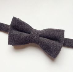 DESCRIPTION: Mens bow tie in beautiful soft dark grey wool FABRIC: 100% Wool  --------------------------------------------------------------------------------------------  DETAILS: • This bow tie is pre-tied • Attached to an adjustable strap fitting approx 15inch - 19inch neck size • Neatly packaged in a smart box with ribbon and tag attached • Lovingly handmade in the UK • Postage - UK delivery is sent first class with proof of postage, all other shipping is sent with air mail and proof of…