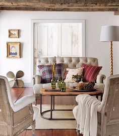 In this 18th-century Connecticut house, dramatic architecture—rough-hewn beams and pitched ceilings—called for simplicity, albeit with serious patina. While the living room's upholstered furniture is white, the sofa and chairs are also purposefully deconstructed, with tufted fronts and exposed burlap-and-wood backs.   - CountryLiving.com
