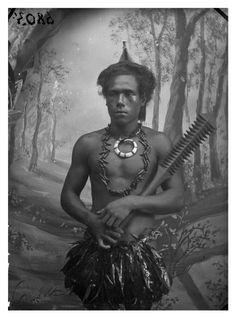 young Samoan man wearing body ornaments, including a high status ulafala (pandanus seed necklace) and aboar's tusk pendant. He holdsa carved club (fa'alaufa'i). AMS318/V6803