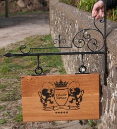 Beautiful hand made wrought iron brackets in an intricate medieval style along with heavy duty rings. The sign is made from oak.  www.sign-maker.net/hanging-house-signs.html