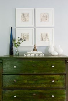 Light blue walls, green chest, white vases, pictures very nice