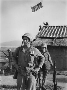 Men of Captain Bob Barrow's company raised a small American flag over the highest rooftop upon the highest hill in Seoul–but even as it was tied into place the sound of firing down the hill attracted their attention … and the flag-raising became just a statement of fact, a minor incident in another day in Korea, September 1950. Photo by David Douglas Duncan