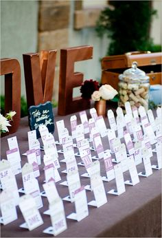 Themed escort cards that stand up on end. Event Design: Jennie J. Events ---> http://www.weddingchicks.com/2014/05/08/fill-your-wedding-with-love-and-adventure/