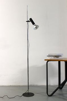 FLOOR LAMP   SARFATTI 1055/SP Gino Sarfatti production Arteluce, 1955 Socket sleeve in black lacquered aluminium which slides along the stem and swivels in all directions. Stem in chrome-plated steel bar. Cast iron base lacquered gray crackle Dimensions: H 190 cm