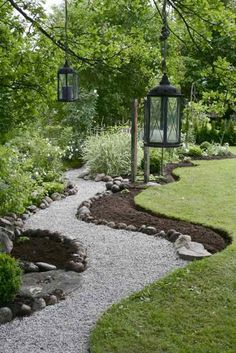 Meandering path and hanging lanterns with a perfect use of pea gravel and tumbled river rock.