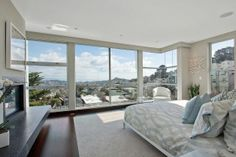The master suite offers floor-to-ceiling windows on two sides and a gas fireplace. Photo: OpenHomesPhotography.com.
