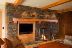 Stone fireplace and accent wall with built-in TV stand. From 1 of 17 projects by Riverland Homes.