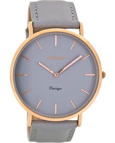 Από τον οίκο Oozoo ένα ρολόι με ροζ χρυσή μεταλλική κάσα και γκρι καντράν με γκρι δέρμα