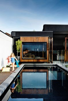 "This 9x3m pool in Melbourne was designed to be ""season-less"", says owner Andy Mullins. ""We wanted it to be an exciting space to dine by, swim in, walk past and look at from inside with the fire going."" A dark-tiled interior is combined with bullnose bluestone tiles and spotted gum decking.   **Cost:** about $85,000.   Photo: Derek Swalwell: [object Object]"