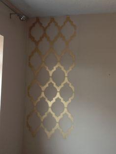 Gold geometric wall print painted onto a shelf