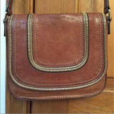 Michael Kors cross body purse Medium brown leather adjustable crossbody purse. Has cool zipper detailing. Also has a pocket in the back and inside the purse. MICHAEL Michael Kors Bags Crossbody Bags