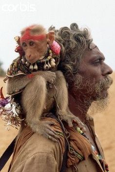 India:Original caption: A singer/storyteller and his costumed monkey perform tricks for tourists visiting the beach. Hanuman, a monkey god in the Hindu pantheon is the loyal friend to Lord Rama in the great Hindu epic the Ramayana.