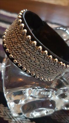 Brett armband med olika flätot och silverkulor i ytterkant
