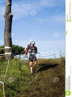 Cyclo cross competitor carrying his bike down a hill during the event at the Acquedotti in Cinecitta park, Rome, Italy.
