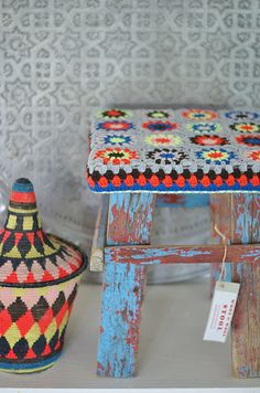 stool/pieces of knitted blankets with tassles on the corners