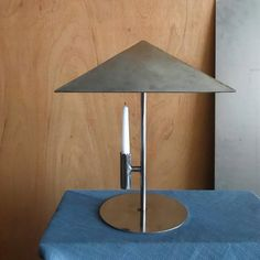 "This candle holder is one of several metalwork pieces created by EJR Barnes during the coronavirus lockdown, while he taught himself how to weld.  The design is Barnes' take on the classic Armani Casa lighting range, which features ""variations of a pyramid on a stick"". Here, this motive is rendered entirely in metal and with a candle instead of a lightbulb. Through The Window, Window Frames, Strip Lighting, Club Chairs, Window Coverings, Furniture Making, Industrial Design, Metal Working, Light Bulb"