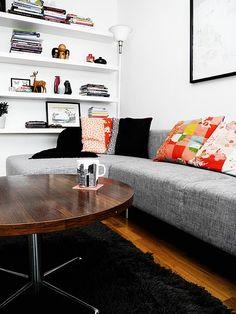 Grey sofa, black rug and dark wood coffee table