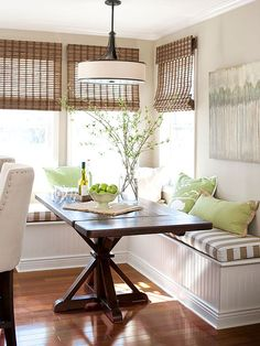 Utilize a sunny kitchen corner with L-shape banquette seating. A simple rectangular table fits snugly against the bench and provides ease of movement in and out of the dining area. Bamboo blinds, muted wall color, and earth-tone upholstery keep the space light and airy./