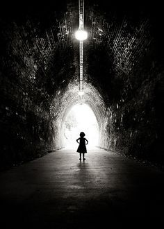 Low key black and white photo of girl in tunnel silhouetted against light at the end of the tunnel