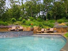 Pictures of Mediterranean-Style Gardens and Landscapes: An arc-shaped pool with a spa is built into the hillside, where cascading water gently laps over the Misty Rose flagstone. Design by Barry Block. From DIYnetwork.com
