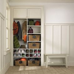 LOVE IT for the mudroom! Organizing coats, shoes, and backpacks is a snap with this simple storage area. Cubbyholes are provided for shoes, while coats and bags hang neatly on hooks. Simple baskets make it easy to pull out needed items while hiding any clutter. Create a similar look by installing a storage space that blends with the color of your walls.