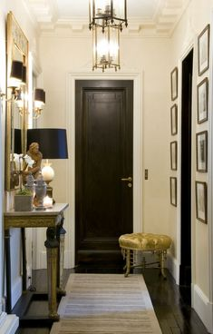 living room / black / neutrals / animal print / gold console table, mirror, lamp, table decor, stool by door, lighting