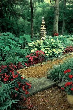 Tall cairn in shade garden surrounded by hostas, begonias, ferns, and impatiens.