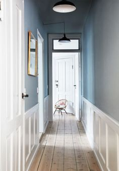 Hallway painted in dusty blue. Industrial pendants in black and white. Hallway painted in dusty blue. Industrial pendants in black and white. Details in white such as high panels in white and patinated wooden floors. Blue Hallway, Hallway Paint, Entry Hallway, Upstairs Hallway, Flur Design, Home Design, Hallway Designs, Hallway Ideas, Hallway Inspiration