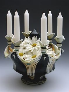 i just really like this piece, how it incorporates flowers, candles, and that center black bulb that peeks above the flowers. i like the glazing and the design and how the candle holders delicately sit on the points, between which the center piece seems to be curled down or peeled open - lorna meaden