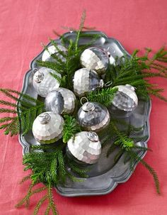 For an easy DIY tablescape, decorate a serving tray with silver ornaments. Tuck in boughs of evergreen for a simple yet elegant centerpiece. More Christmas centerpiece ideas: http://www.midwestliving.com/homes/seasonal-decorating/easy-christmas-centerpiece-ideas/?page=6