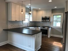 Renovated vintage farmhouse style kitchen| black and white | Gray Owl paint | hardwood floors | Shaker style cabinets | Black leathered granite countertops | Pottery barn pendants | Stainless steel appliances | Farmhouse sink