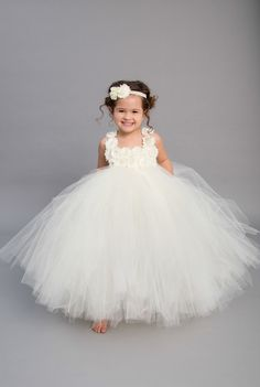 Make your wedding stand out with this beautiful Ivory Flower Girl Dress. This multilayer dress is made with yards and yards of premium soft tulle. Embellished with two rows of ivory flowers featuring rhinestone encased faux pearls. The double ivory satin straps lay over the shoulders and tie in the back into one large bow.  Big bow on back available by request.  The listed length is for a measurement from armpit to hem.  **Please measure from underneath the armpit to the floor or top of…